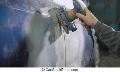 worker is brushing off old blue dye from automobile body...