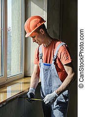 Worker is checking the correctness of the installation of a window sill.