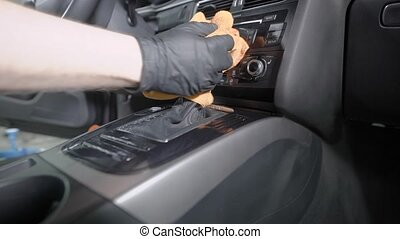 worker is cleaning handle of gearbox and control panel inside automobile in a car washing service