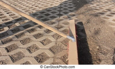Worker is cleaning modern cobblestone with red broom -...