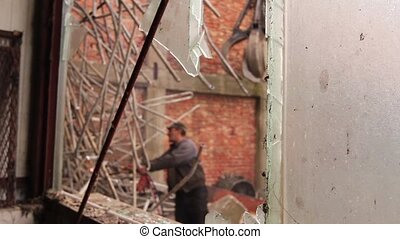 Worker is cutting manually old metal construction using...