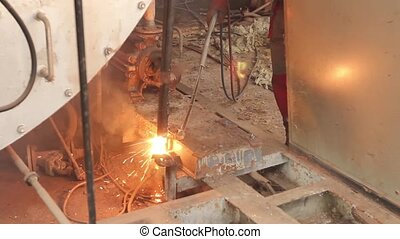 Worker is cutting obsolete industrial equipment with...