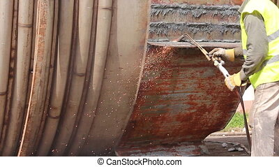 Worker is cutting old metal industrial equipment with...