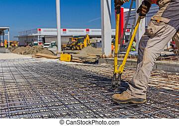 Worker is cutting rebar with scissors for reinforcement bars.