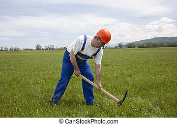Worker is Digging by Pickaxe on a Green Field