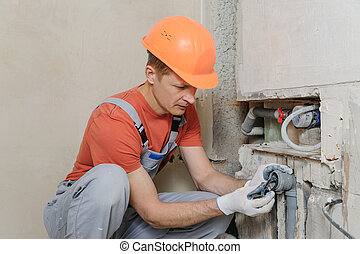 Worker is installing sewer pipes in a kitchen of a apartment.