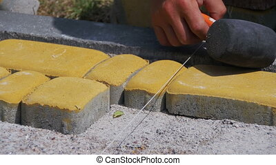 Worker is Laying Paving Stones using Hammer. Construction...