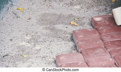Worker is Laying Paving Stones using Hammer. Slow Motion in...
