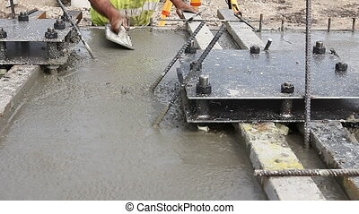 Worker is leveling concrete after pouring - Mason is using a...
