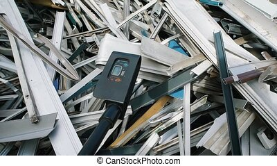 worker is measuring ionizing radiation of heap of scrap...