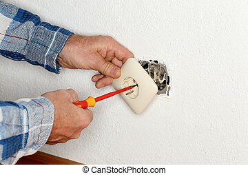 worker is mounting an electrical socket