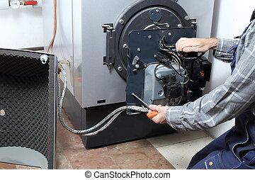 worker is repairing a heating burner in a house
