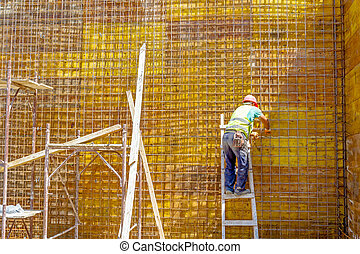 Worker is tying rebar to make a newly reinforcing grid in wooden mold for concrete pouring
