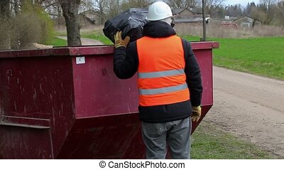 Worker keeps garbage bag on waste