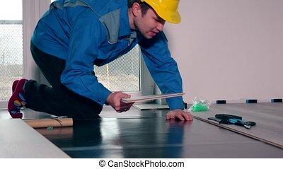 worker lay laminate floor. dolly sliding movement shot.
