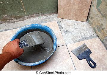 worker laying ceramicson floor