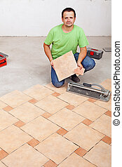 Worker laying floor tiles on concrete surface