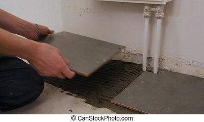 Worker laying tiles on floor
