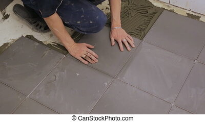 Worker laying tiles on floor