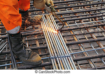 Worker legs in orange clothes weld metal grating by ...
