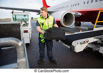 Worker Lifting Luggage From Conveyor Attached To Airplane