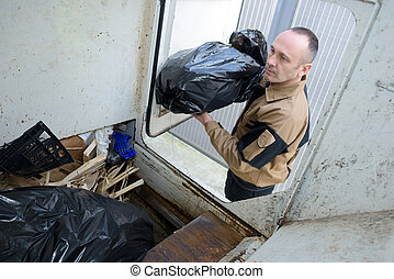 Worker loading rubbish bags