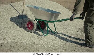 worker loads gravel into a wheelbarrow