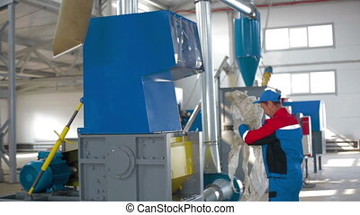 Worker loads sorted plastic in automated plastic recycling...
