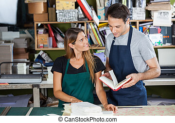 Worker Looking At Colleague Holding Book In Paper Factory