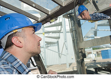 worker looking at rear view mirror