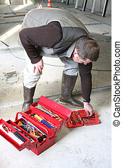 Worker looking for a tool in his toolbox