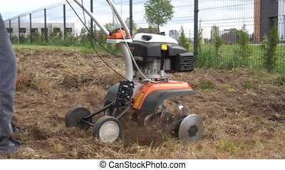 worker loosen soil with cultivator tractor urban townhouse yard. Gimbal movement