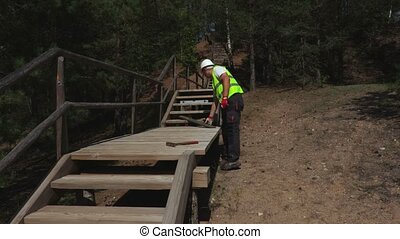 Worker makes a wooden staircase