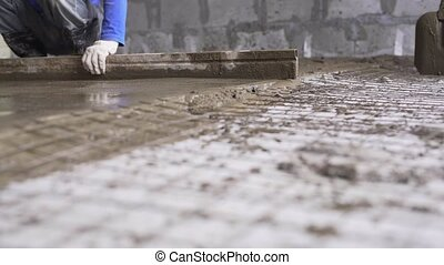 Worker making cement screed on the floor view