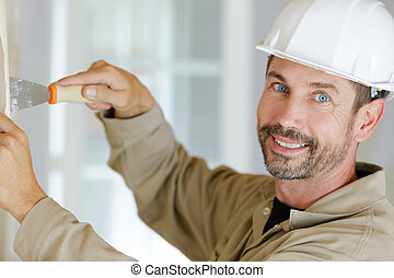worker making repair in room wallpapering on wall