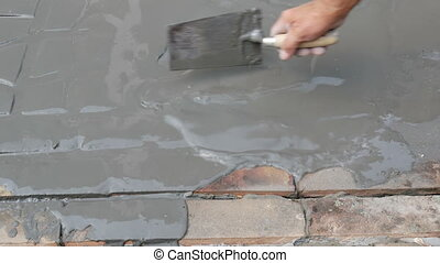 Worker making tile floor - Worker spreading mortar to...