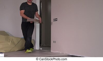 Worker man carry laminate floor boards in new apartment