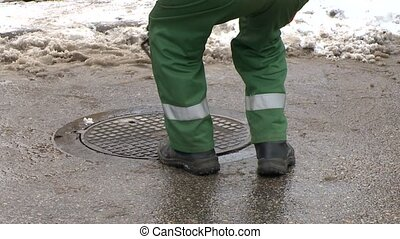 Worker man close drainage sewage well hole on street in...