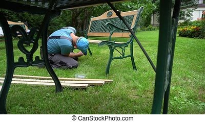 Worker man disassemble retro bench in parts. Outdoor ...