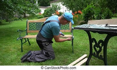 Worker man disassemble retro bench. Outdoor furniture ...