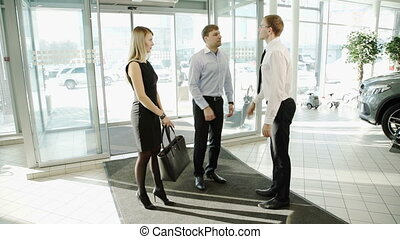 Worker man in automotive center meets couple client to display cars