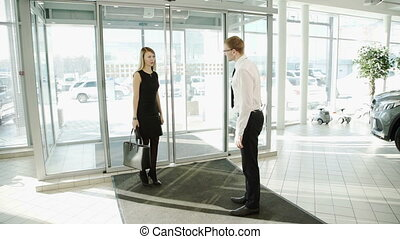 Worker man in automotive center meets woman client to...
