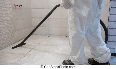 Worker man in white overall clean construction remains and dust vacuum cleaner