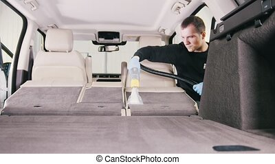Worker man is cleaning of vehicle interior with vacuum cleaner
