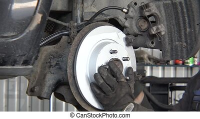 worker man mounting new brake disk on old car lifted in repair shop.