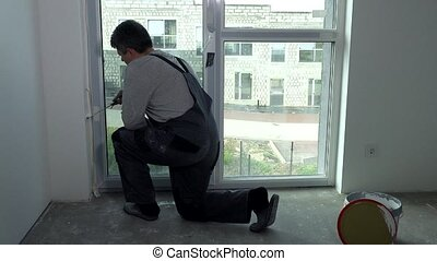 Worker man paint wall near window with roller