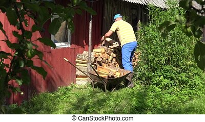 worker man placing log in row along home wall in sunny day....