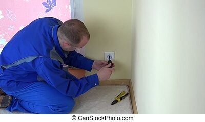 Worker man repair an electrical outlet in apartment