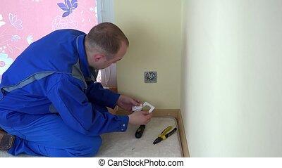 Worker man repair an electrical wall socket at work