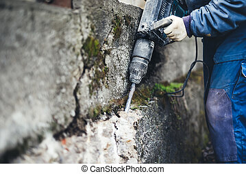 worker man using a jackhammer to drill into wall. professional worker in construction site